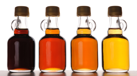 Different grades of maple syrup in bottles